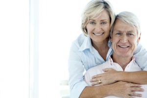 Happy senior couple with her arms around him